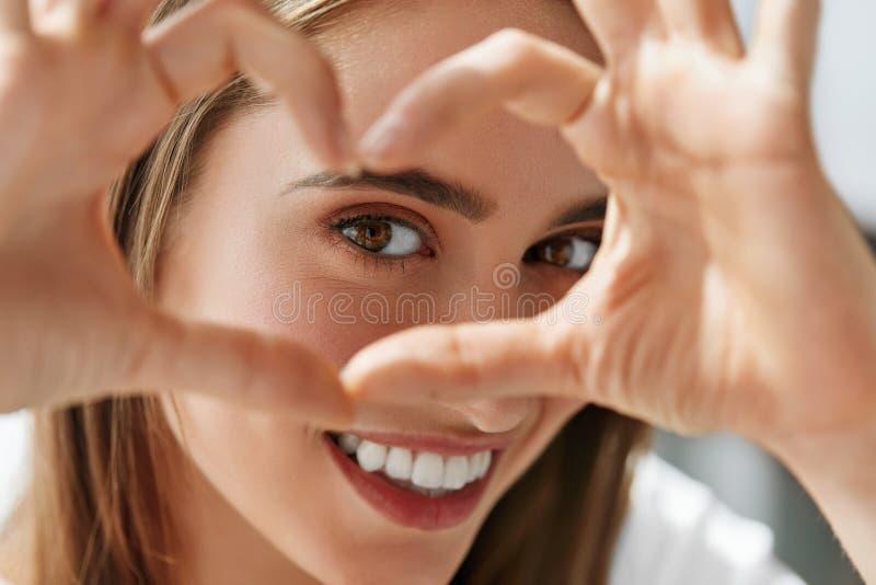 La mujer feliz hermosa que muestra la muestra del amor cerca observa foto de archivo