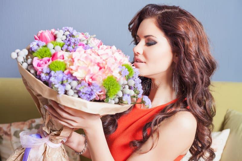 La mujer feliz hermosa recibió un ramo de la flor de rosas fotos de archivo
