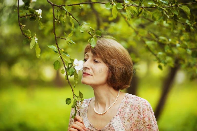 La mujer feliz inhala el aroma de una flor fotos de archivo libres de regalías