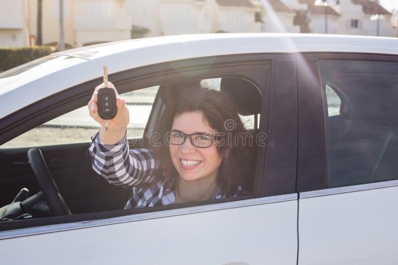 La mujer feliz joven atractiva muestra llaves del nuevo coche fotos de archivo libres de regalías