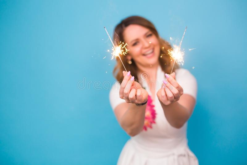 La mujer feliz joven con las bengalas celebra y ríe en fondo azul imagen de archivo libre de regalías