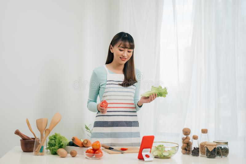 La mujer feliz joven en el delantal que mira receta en tableta en la cocina Ensalada vegetal Concepto de dieta Forma de vida sana fotos de archivo libres de regalías