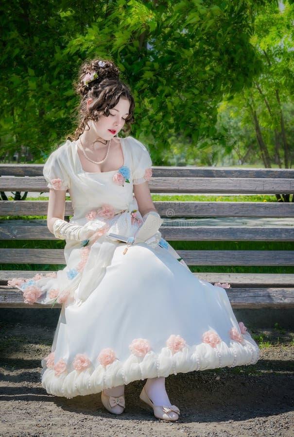La mujer feliz joven en un vestido blanco largo elegante de la novia está leyendo b fotografía de archivo libre de regalías