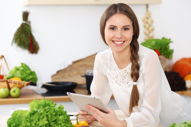 La mujer feliz joven está haciendo compras en línea por la tableta mientras que sonríe Ama de casa que busca una nueva receta FO fotografía de archivo libre de regalías