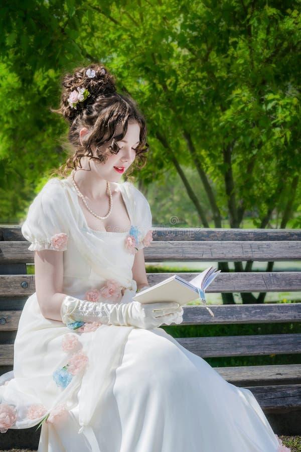 La mujer feliz joven está leyendo un libro que se sienta en un banco imágenes de archivo libres de regalías