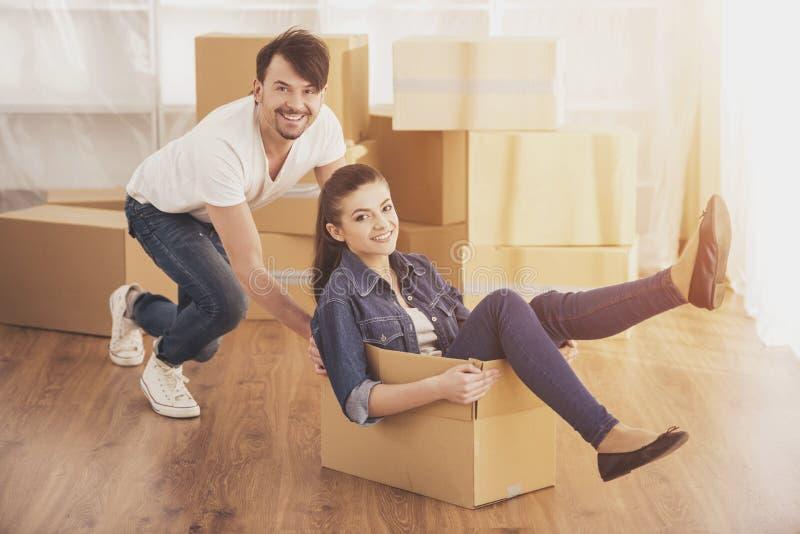 La mujer feliz joven que se sienta en una caja de cartón Mudanza, compra de la nueva habitación foto de archivo