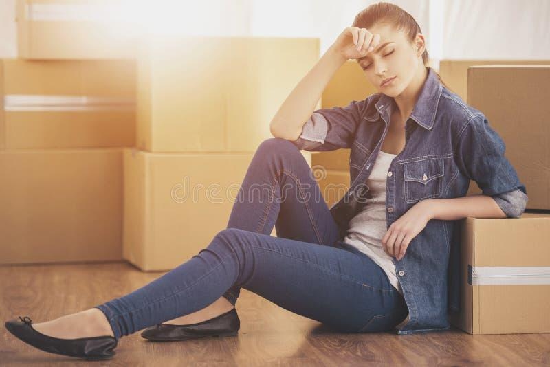La mujer feliz joven se sienta en un cuarto cerca de las cajas Mudanza, compra de la nueva habitación imagenes de archivo