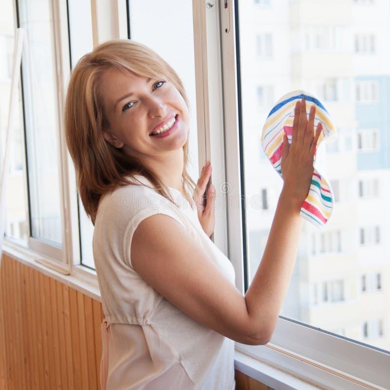 La mujer feliz lava la ventana en el nuevo apartamento foto de archivo