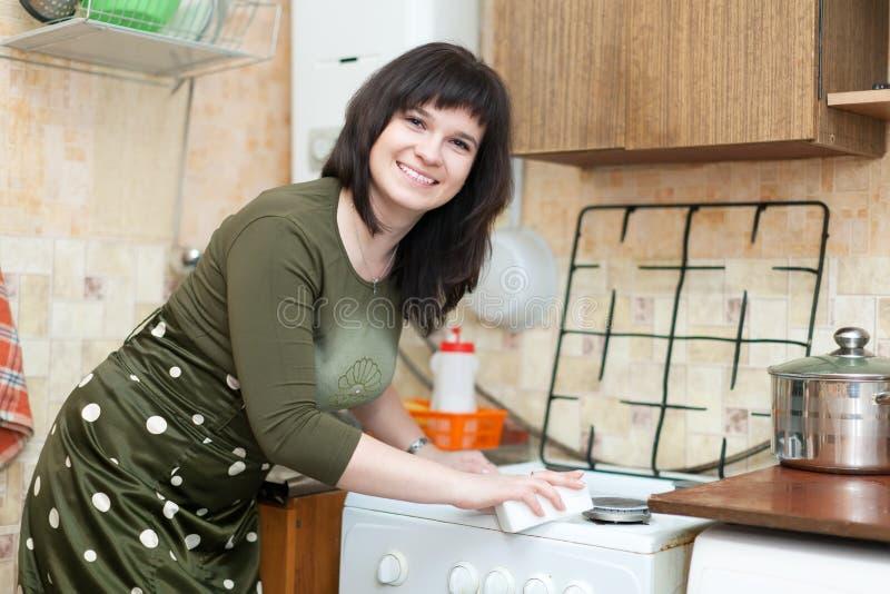 La mujer feliz limpia la estufa de gas fotos de archivo libres de regalías