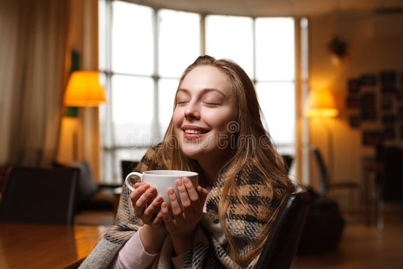 La mujer feliz magnífica bebe el café en un fondo del café Tela escocesa acogedora cubierta imagen de archivo