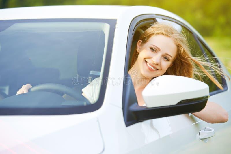 La mujer feliz mira hacia fuera la ventanilla del coche en la naturaleza fotos de archivo