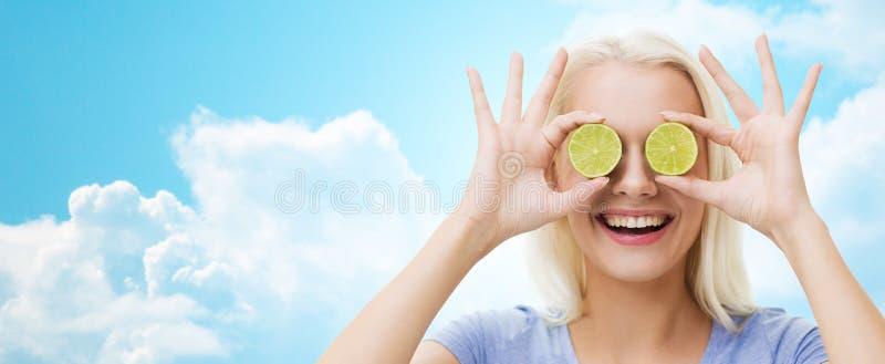 La mujer feliz que tiene cubierta de la diversión observa con la cal foto de archivo