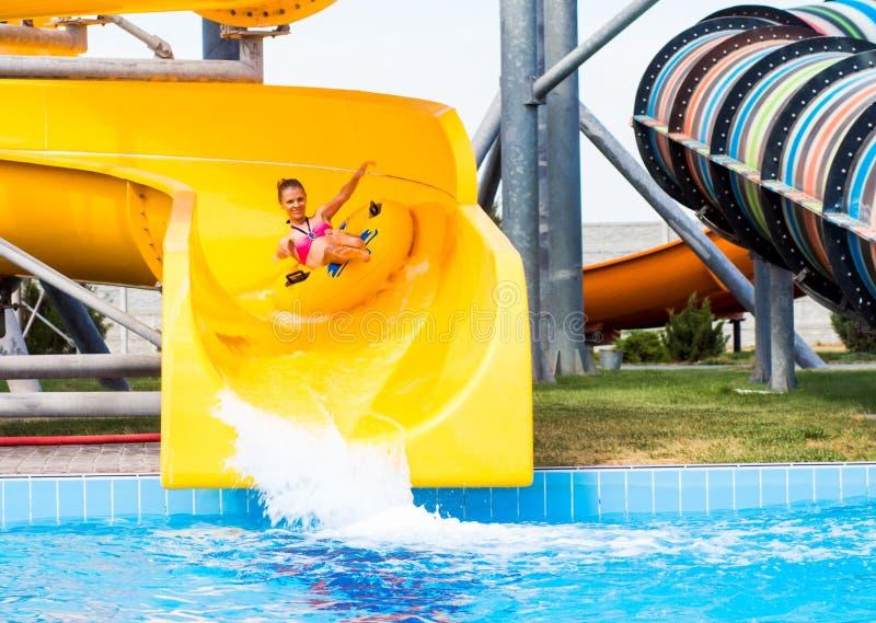 la mujer feliz que va abajo en el anillo de goma por la diapositiva anaranjada en la aguamarina parquea Vacaciones de verano imágenes de archivo libres de regalías