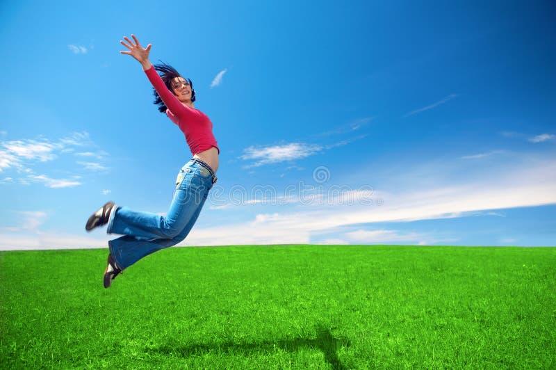 La mujer feliz salta en campo foto de archivo