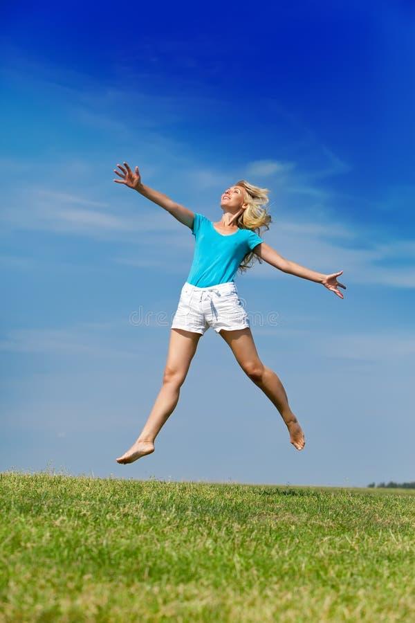 La mujer feliz salta en un campo del verde del verano contra el cielo azul. Retrato en un día soleado foto de archivo libre de regalías