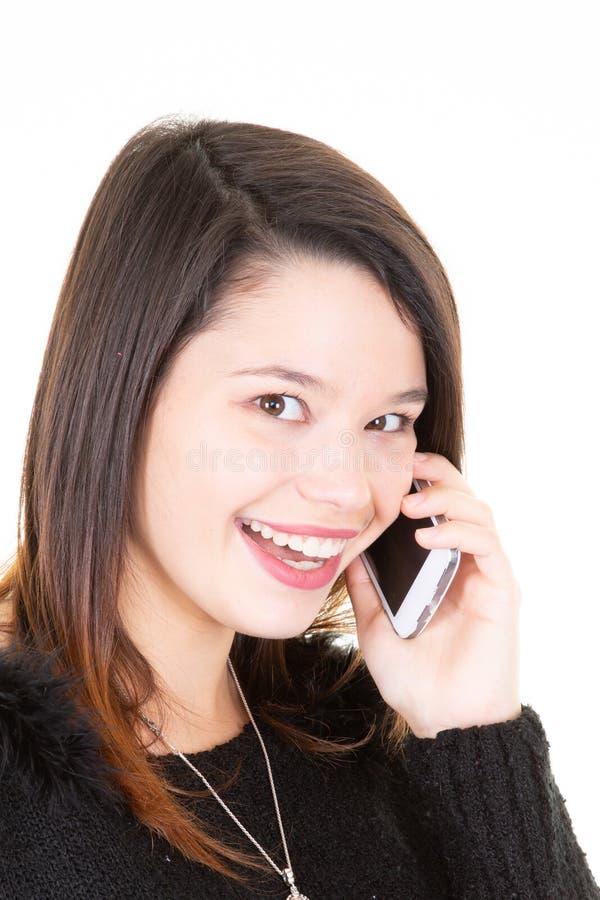 La mujer feliz sonriente joven con el pelo largo está hablando en el teléfono sobre el fondo blanco fotos de archivo