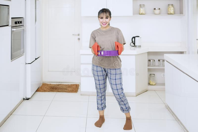 La mujer feliz sostiene una bandeja que cuece en la cocina imagen de archivo libre de regalías