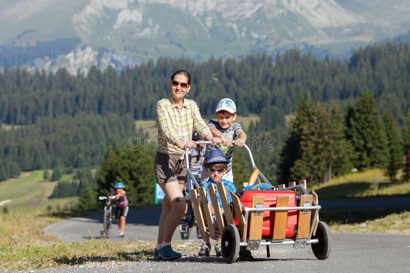 La mujer feliz y dos muchachos están caminando con equipaje en centro turístico de montaña imágenes de archivo libres de regalías