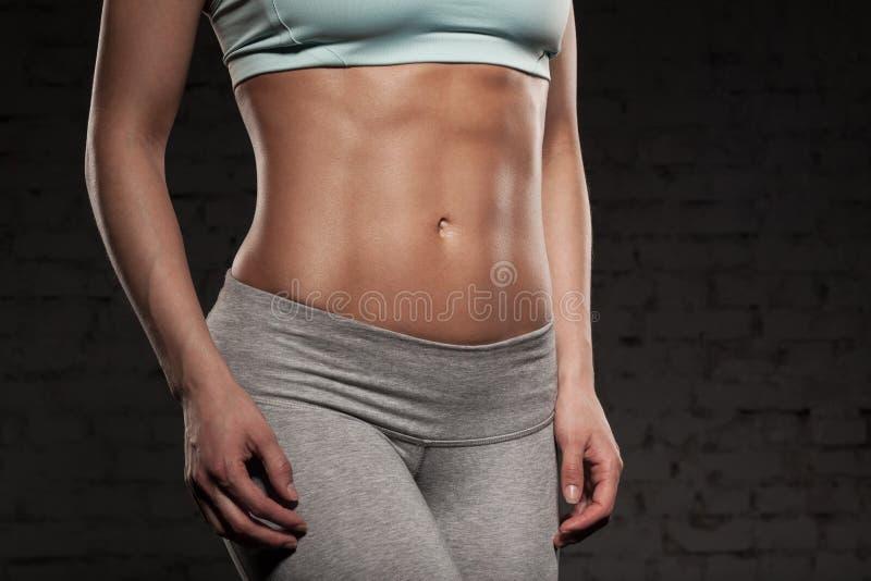 La mujer femenina de la aptitud con el cuerpo muscular, hace su entrenamiento, ABS, abdominals imagen de archivo