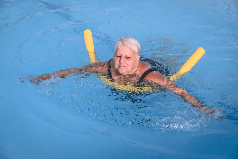 La mujer femenina mayor se aferra a un dispositivo de flotación en una piscina para aprender cómo nadar imagen de archivo