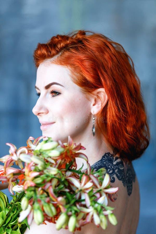 La mujer femenina romántica encantadora sostiene Gloriosa anaranjado en fondo azul foto de archivo