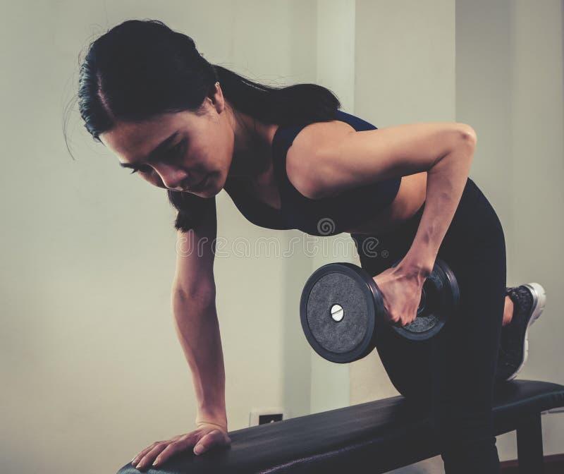 La mujer flaca fuerte está levantando pesa de gimnasia foto de archivo libre de regalías