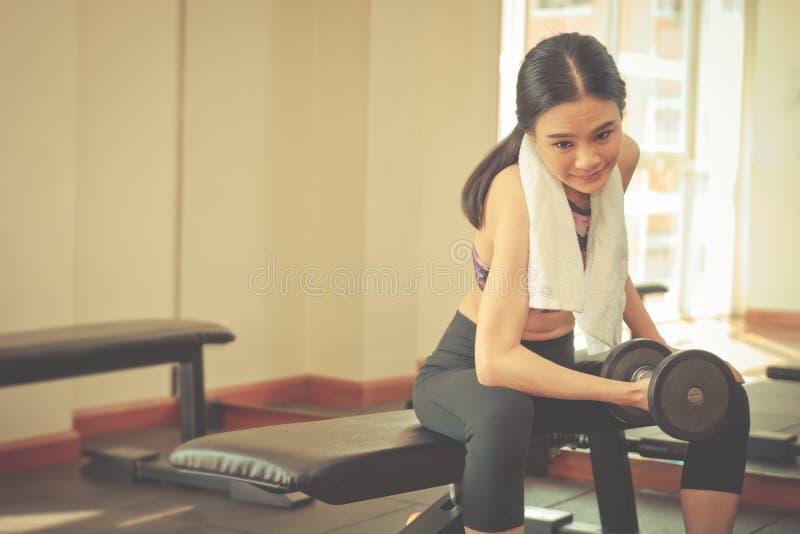 La mujer flaca fuerte está levantando pesa de gimnasia en aptitud imagen de archivo libre de regalías
