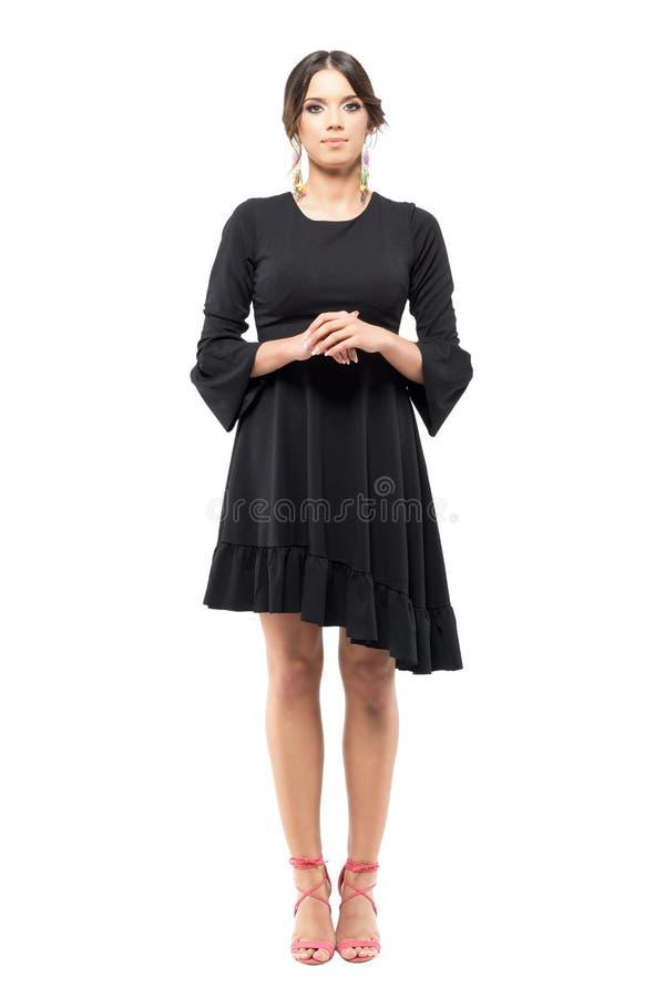 La mujer formal con clase derecha en vestido negro con la mano abrochó la mirada de la cámara fotos de archivo