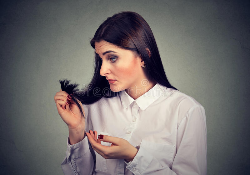 La mujer frustrada infeliz la sorprendió es pelo perdidoso, extremos partidos notados fotografía de archivo