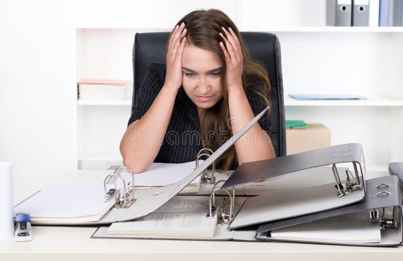 La mujer frustrada joven se está sentando delante de una pila de ficheros fotos de archivo libres de regalías