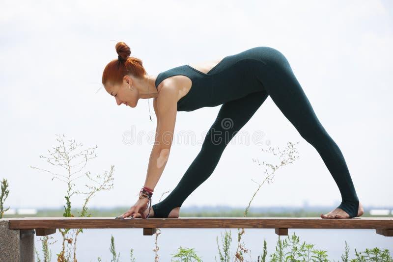La mujer fuerte atl?tica que practica yoga dif?cil presenta al aire libre fotos de archivo