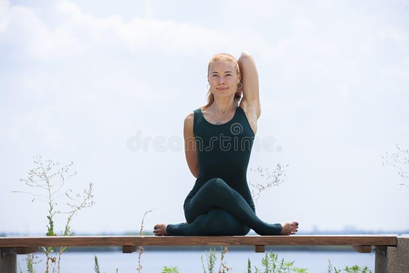 La mujer fuerte atl?tica que practica yoga dif?cil presenta al aire libre imagen de archivo