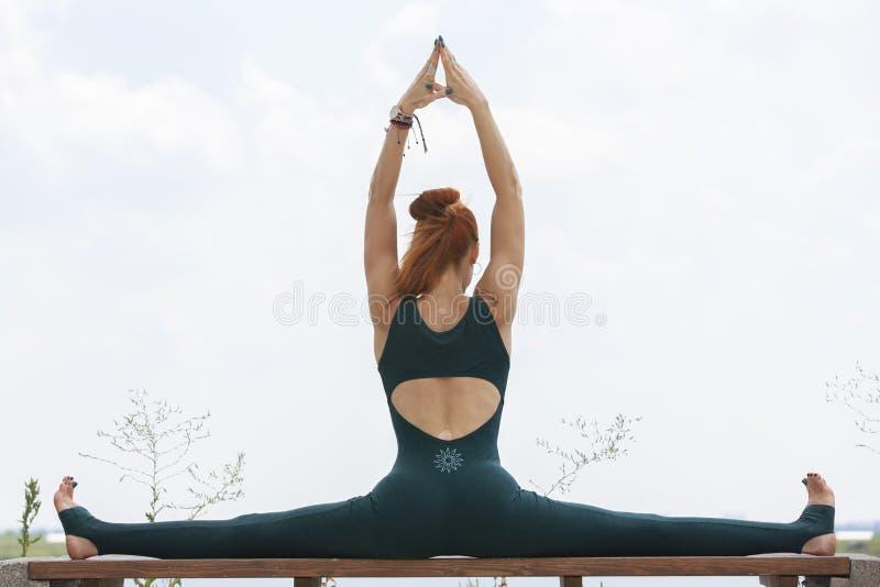 La mujer fuerte atl?tica que practica yoga dif?cil presenta al aire libre fotografía de archivo libre de regalías