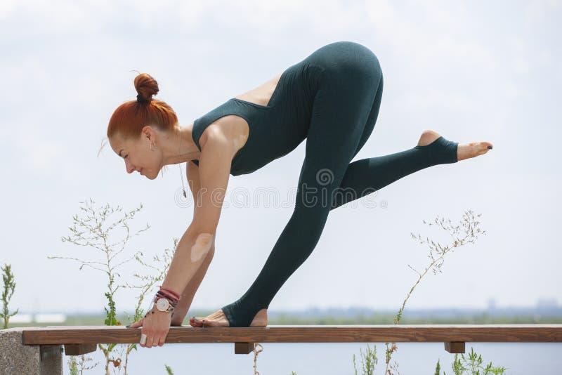La mujer fuerte atl?tica que practica yoga dif?cil presenta al aire libre imágenes de archivo libres de regalías