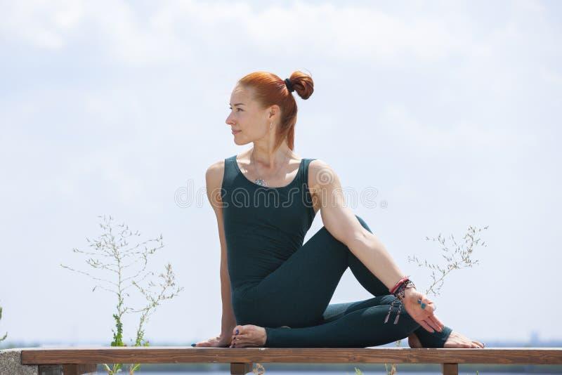La mujer fuerte atl?tica que practica yoga dif?cil presenta al aire libre foto de archivo