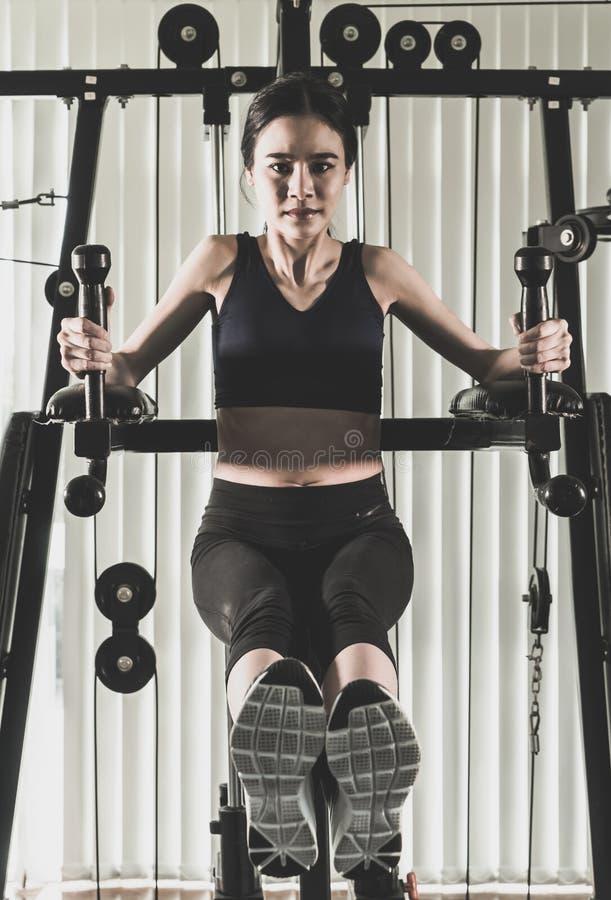 La mujer fuerte está entrenando en la máquina del gimnasio de la aptitud imagen de archivo