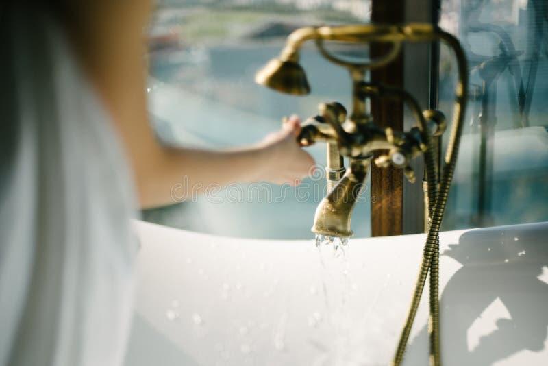 La mujer gira el agua en el grifo en el cierre del cuarto de ba?o para arriba foto de archivo libre de regalías