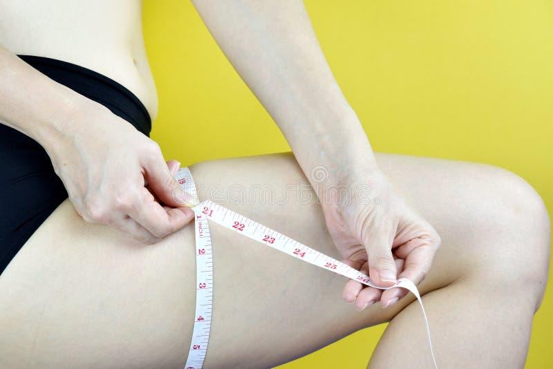 La mujer gorda comprueba su muslo con la cinta métrica foto de archivo libre de regalías