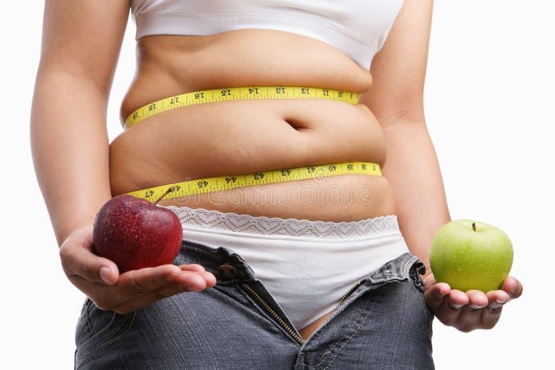 La mujer gorda con desabrocha los pantalones vaqueros que sostienen la manzana imagenes de archivo