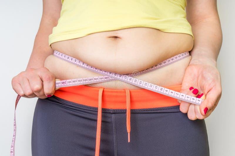 La mujer gorda con la cinta está midiendo la grasa en el vientre fotografía de archivo