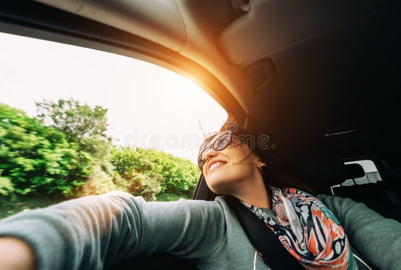 La mujer goza con la visión desde la ventanilla del coche en viajar en auto foto de archivo libre de regalías