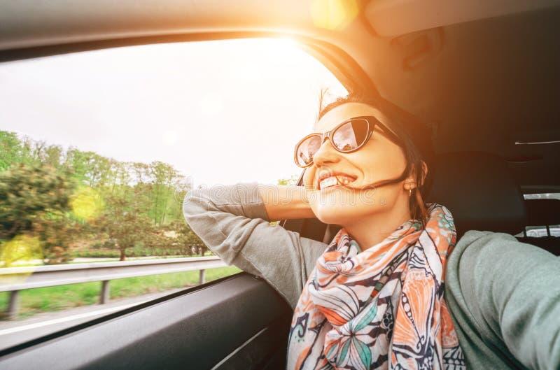 La mujer goza con la visión desde la ventanilla del coche al viajar en auto imagen de archivo libre de regalías