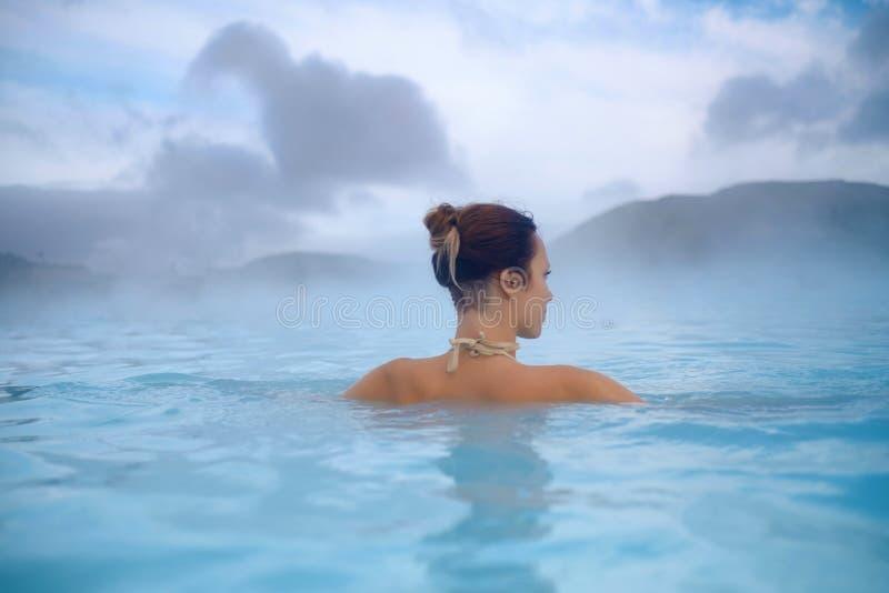 La mujer goza del balneario en aguas termales geotérmicas fotografía de archivo libre de regalías