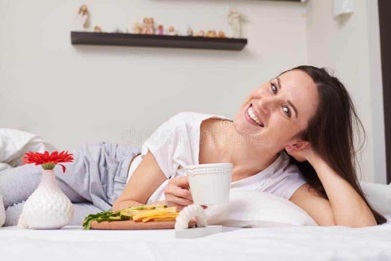 La mujer goza del desayuno romántico mientras que se relaja en cama fotografía de archivo