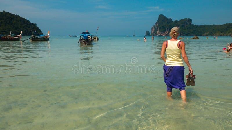 La mujer goza el caminar a lo largo del agua en la playa de Krabi, Tailandia foto de archivo