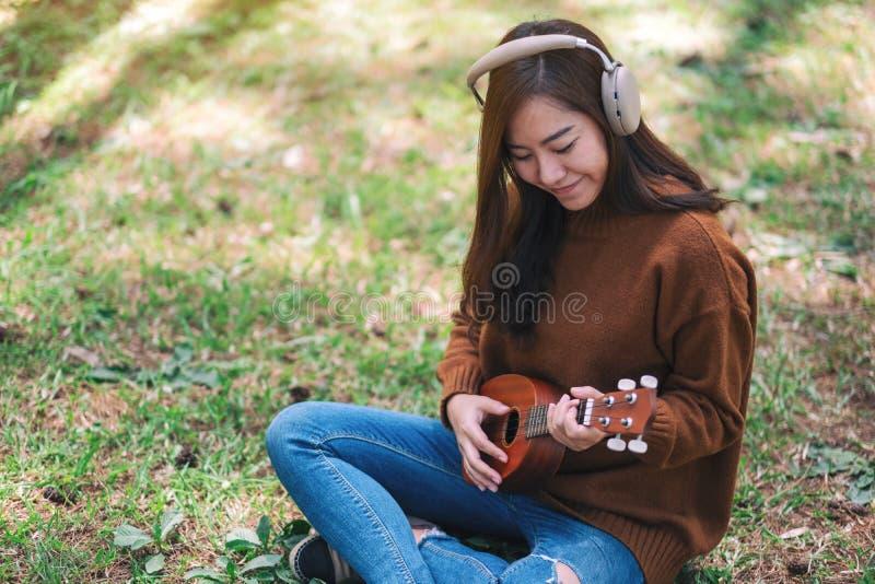 La mujer goza el escuchar la música con el auricular mientras que juega el ukelele en el parque imagenes de archivo