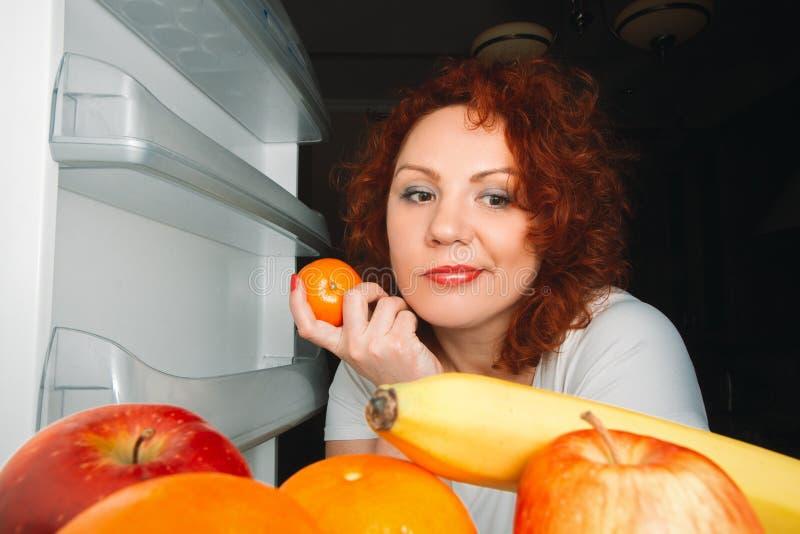 La mujer grande come la fruta Muchacha gorda del pelo rojo que mira el refrigerat interior foto de archivo libre de regalías
