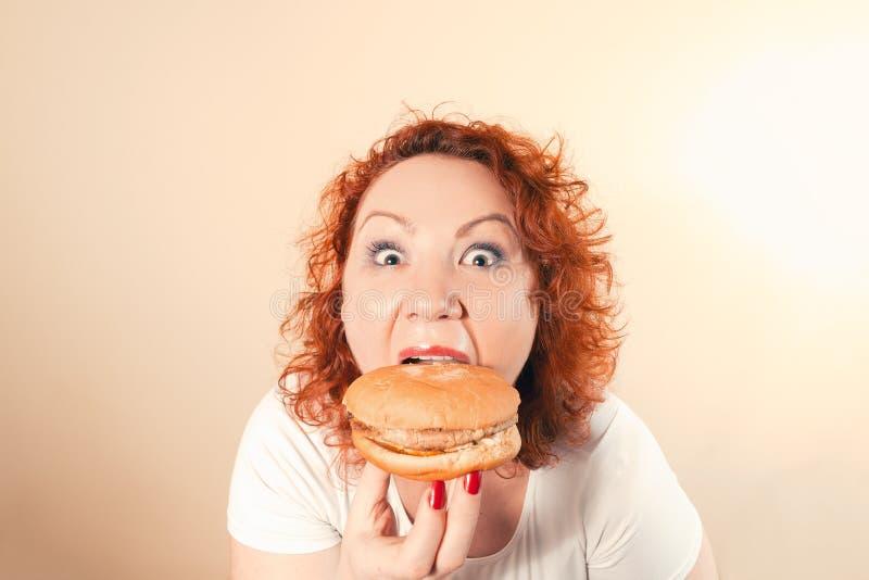 La mujer grande come los alimentos de preparación rápida Muchacha gorda del pelo rojo con la hamburguesa Unhealth foto de archivo