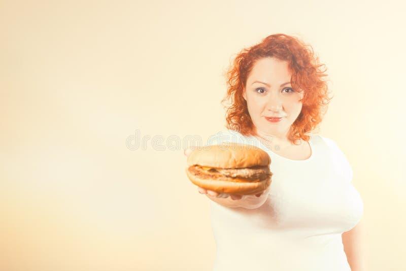 La mujer grande come los alimentos de preparación rápida Muchacha gorda del pelo rojo con la hamburguesa Unhealth fotos de archivo libres de regalías