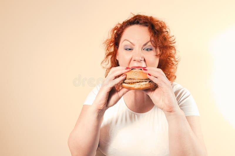 La mujer grande come los alimentos de preparación rápida Muchacha gorda del pelo rojo con la hamburguesa Unhealth imagen de archivo libre de regalías